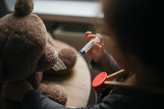 Little girl doing injection to sick teddy bear toy closeup.