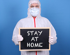 Doctor with a blackboard and message Stay at Home