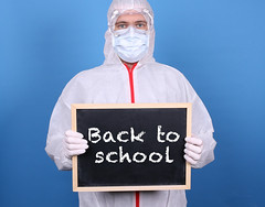 Doctor with a blackboard and message Back to School