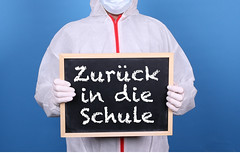 Doctor in protective clothing showing blackboard with Zurück in die Schule message