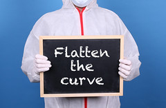 Doctor in protective clothing showing blackboard with Flatten the Curve message