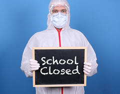 Doctor with a blackboard and message School CLosed