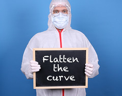Doctor with a blackboard and message Flatten the Curve