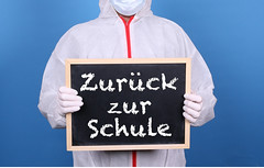 Doctor in protective clothing showing blackboard with Zurück zur Schule message
