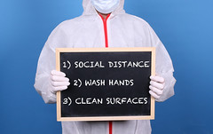 Doctor in protective clothing showing blackboard with instructions how to fight Coronavirus