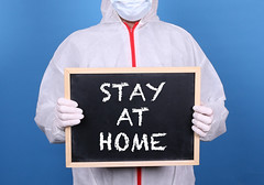Doctor in protective clothing showing blackboard with Stay at Home message