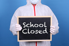 Doctor in protective clothing showing blackboard with School Closed message