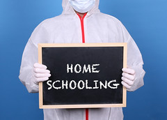 Doctor in protective clothing showing blackboard with Home Schooling message