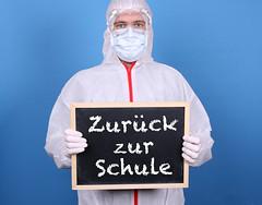Doctor with a blackboard and message Zurück zur Schule