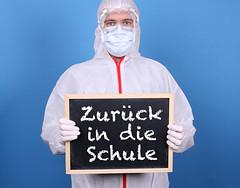 Doctor with a blackboard and message Zurück in die Schule