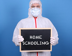 Doctor with a blackboard and message Home Schooling