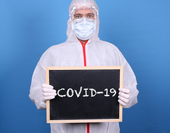 Doctor with a blackboard and message COVID-19