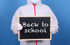 Doctor in protective clothing showing blackboard with Back to School message