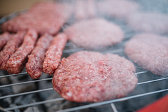 Hamburgers on a hot barbecue with smoke.