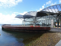 Geelong. Cafe on the pier on Corio Bay. Note the Geelong Baths Swimming Club painted bollards on the edge of the esplanade.