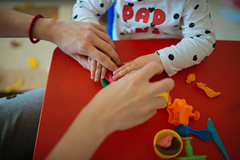 Mother and daughter have fun with colorful plasticine.