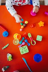 Little preschool girl making plasticine. View from above.