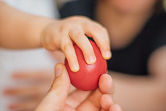 Child taking an easter egg from parent's hand