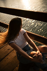 Young woman sitting near the lake and enjoys the sunset.