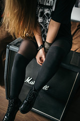 Rock hipster girl with beautiful hair sitting on Marshall guitar cabinet.