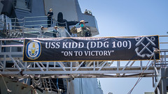 A Sailor salutes the national ensign as he disembarks USS Kidd (DDG 100) at Naval Base San Diego, Calif.