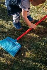 Kleinkind spielt mit einem Besen im Garten