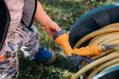 Kleinkind spielt mit der Gartenschlauch Sprüh-Pistole