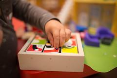 Child`s arm on colorful blocks.