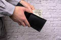 Elegant man in suit pulls out his money from wallet. Conception of money management