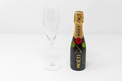 Mini-Flasche von Moët & Chandon Impérial mit einem leeren Sektglas: die Miniaturversion einer wahren Champagner-Ikone