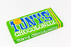 Tony's Chocolonely chocolate bar with almonds and sea salt in a green package on white background: 100% slave free