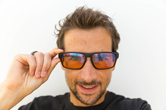 Smiling man wearing the computer glasses designed by Horus X for gamers and people who spend many hours in front of the screen