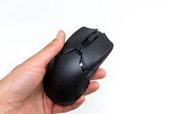Hand holds the Viper Ultimate wireless gaming mouse by Razer in black, close-up on a white background