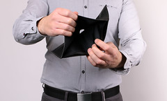 Man holding empty wallet. No money