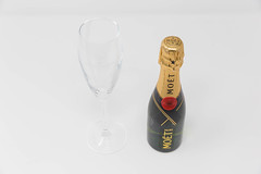 Miniature champagne: a bottle of Mini Moët with an empty champagne glass on a white background