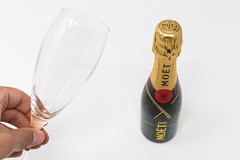 Man holding an empty champagne glass in the hand next to a bottle of Mini Moët on white background