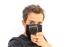 Man wearing non-medical face mask shows the comb attachment of the Philips QC5115/15 hair clipper. Portrait with white background