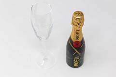Mini Moët Flasche mit leerem Champagnerglas auf weißem Hintergrund