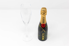 A mini bottle of Moët & Chandon Impérial with an empty champagne glass on white background: the miniature version of a real champagne icon