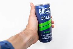 Ein Mann hält eine Dose NOCCO BCAA Birne in der Hand. Dieses koffeinhaltige, zuckerfreie Fitnessgetränk ist von Nocco - No Carbs Company aus Schweden - hergestellt