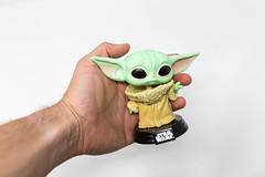 Mann hält die Baby Yoda Pop! Vinylfigur von Star Wars in der Hand vor weißem Hintergrund