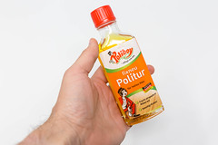 Hand hält eine Flasche fixneu Politur vor weißem Hintergrund. Die Möbelpflege für helles Holz von Poliboy