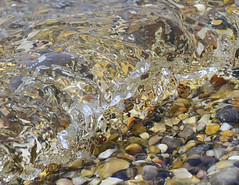 Small wave lapping over stones on a Lake Michigan beach in Leland, MI 04-25-2020 024