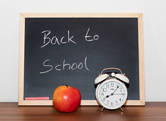 Back To School written on a Blackboard with Apple and Vintage Timer Clock in front of it