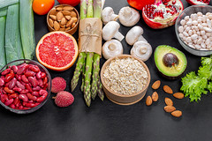 Top View Food Photo of Healthy Ingredients like Red Beans, Oatmeal, Avocado, Almonds, Mushrooms, Asparagus and Grapefruit on Black Background