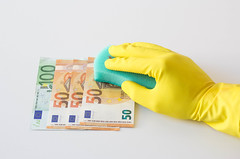 Person with Cleaning Gloves wiping Euro Banknotes with a Sponge on White Background