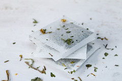 Close Up Photo of stacked Tea Bags with Dried Tea on White Background