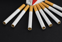 Close Up Photo of Marlboro Cigarettes with Pack of Cigarettes in the Background on Black Table