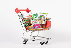 Close Up Photo of Miniature Shopping Cart full of different Groceries on White Background