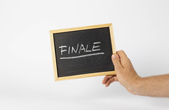 Person holding a small Blackboard with the Word Finale written on it on White Background